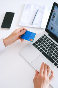 person holding credit card in front of laptop